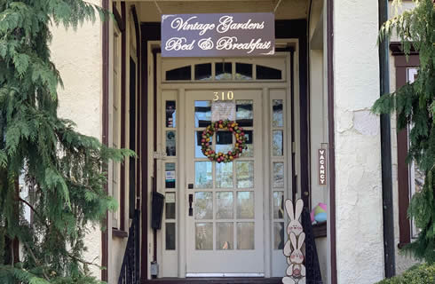 Entryway with a wood and glass door with a sign overhead: Vintage Gardens Bed & Breakfast