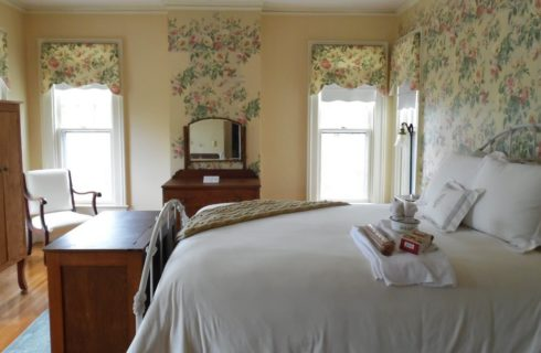 Bedroom with floral wallpaper accents with white iron bed with white bedding and wooden cabinets.