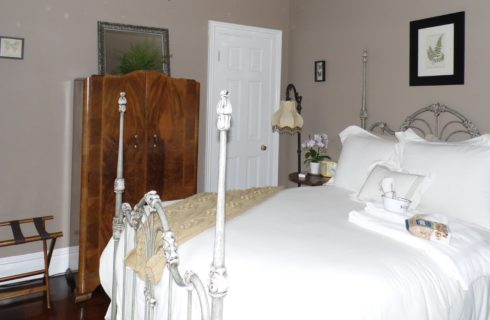 Room with beige walls, antique wooden wardrobe, and white iron bed made up in fluffy white bedding.