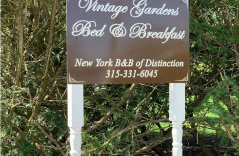 Brown metal sign on white and gold legs with text: Vintage Gardens Bed & Breakfast