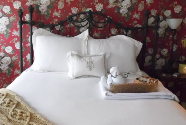 Bedroom with red floral wallpaper, white trim and a black iron bed made up with white bedding next to a white radiator.