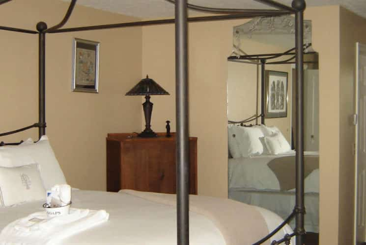 Graceful beige guestroom with a large iron canopy bed made up in white bedding, a dresser and mirror.