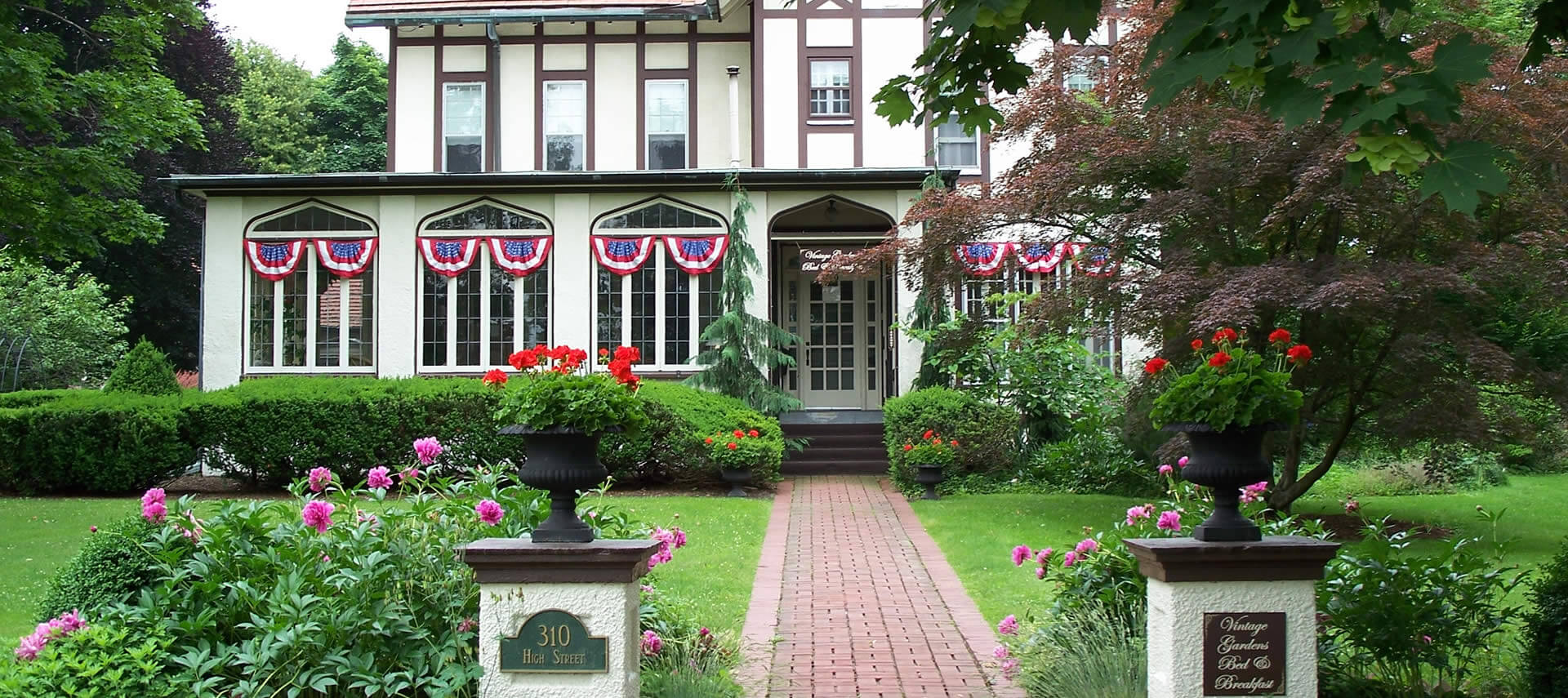Large Tudor home decorated with red white and blue bunting.