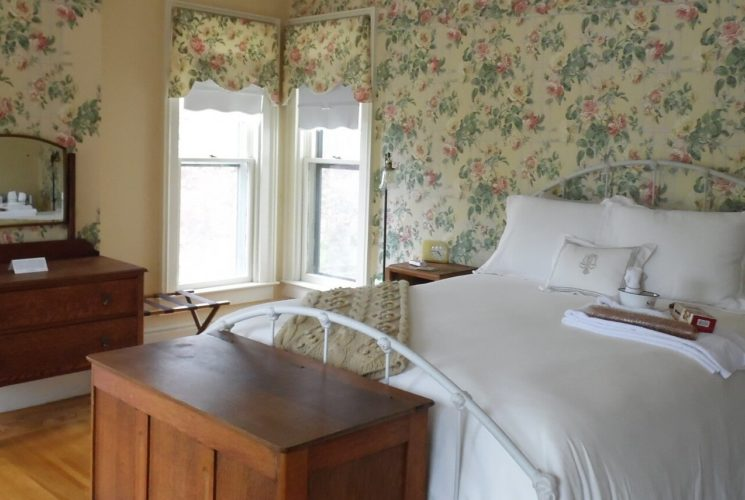Guestroom with floral wallpaper holds an iron bed with white bedding.