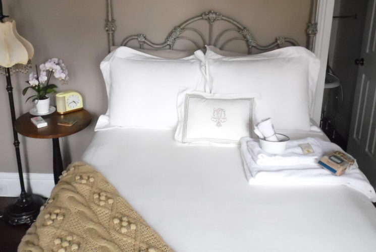 Ornate iron bed made up in fluffy white bedding with a wooden side table.