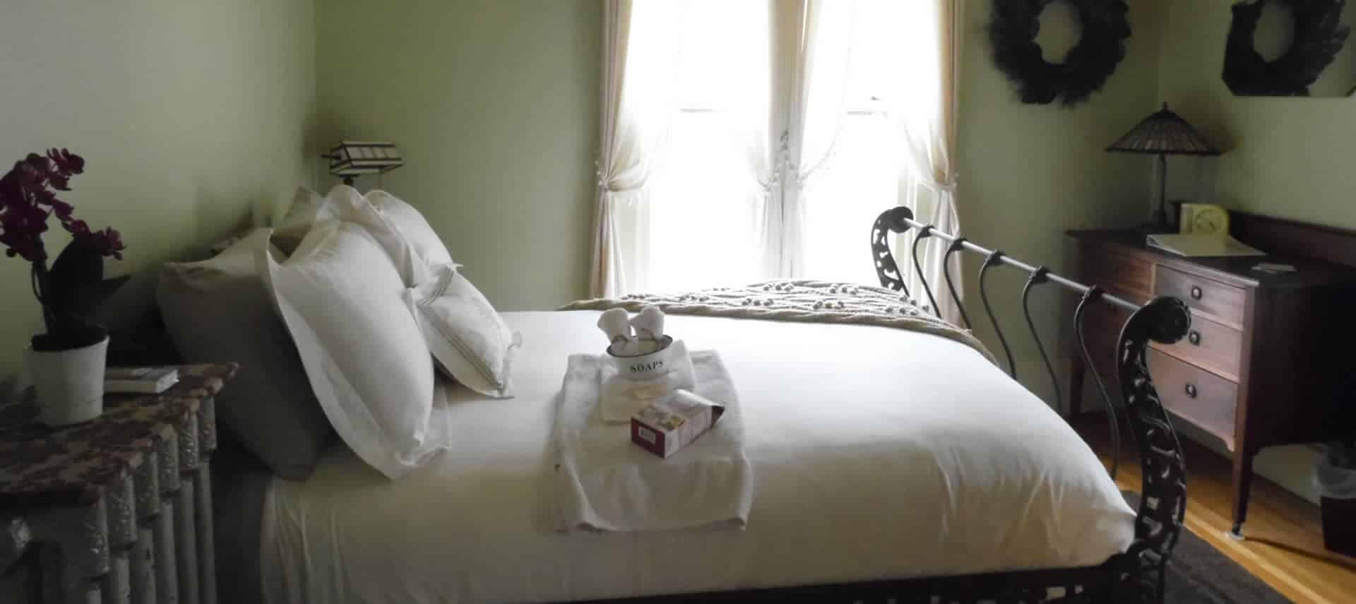 A guestroom with pale green walls holds dark wood furniture, an ornate iron bed with white bedding and a large window.