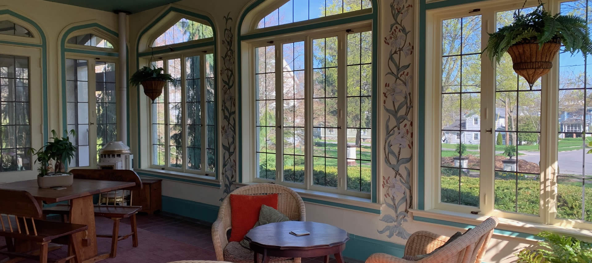 Custom painted sun room with many unique windows and tables and chairs.