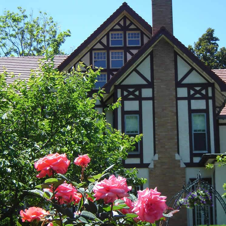 Tudor house with brick fireplace fronted by a pink rosebush.