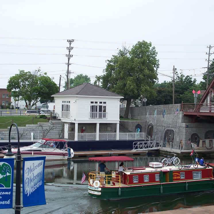 A large houseboat floats by a harbor wall with a small white building on top.