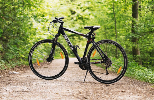 A black cruiser bike sits on a path through the woods.