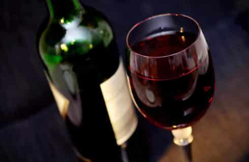 A bottle of red wine along with a wine glass full of red wine.